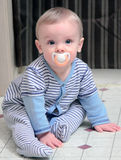 Baby and Binky. Beautiful baby boy with blond hair, blue eyes, and soft, fair complexion with pacifier in mouth, sitting on linoleum floor Royalty Free Stock Photos