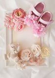 Baby birth frame background. Close-up of photo frame, baby shoes and flowers Stock Photos