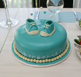 Baby boy birthday cake. Table setting with a blue birthday baby cake and baby shoes on top of it Stock Image