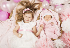 Baby birthday party gifts. Girl holding newborn sister hand. Chi Stock Image