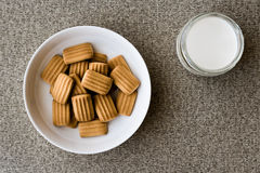 Baby biscuit with milk in white bowl. Royalty Free Stock Images
