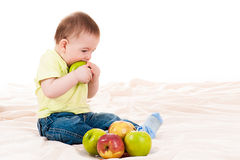 Baby bites the apple Stock Photos