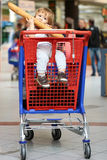 Baby biting French bread in shopping trolley Stock Images