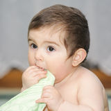 Baby biting green towel Stock Photos