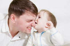Baby biting nose of his father Stock Photos