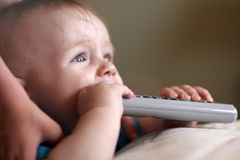 Baby is biting remote Stock Photography