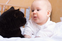 Baby with black cat. Cute five month baby with black cat stock photo