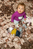 Baby on blanket. Portrait of a cute baby girl sitting on a patterned blanket with toys, looking up curiously Royalty Free Stock Photography