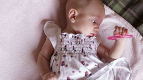 Baby is on blanket  with teeth toy stock video
