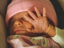 Baby blocking light from her eyes. Small baby blocking light from her eyes in a pink cap stock photo