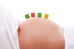 Baby Blocks on a Pregnant Woman's Stomach. A set of baby blocks spelling out 'BABY' are balanced on the stomach of a pregnant woman. Horizontal shot. Isolated on Royalty Free Stock Image