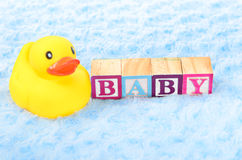 Baby blocks spelling baby. And a rubber duck Stock Images