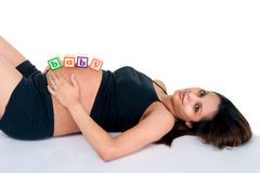 Baby Blocks On Stomach. A young pregnant woman is lying down with baby blocks on her stomach spelling baby royalty free stock image