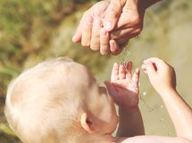 Baby blond beach water game mom royalty free stock photo