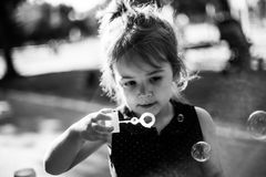 Baby blowing bubbles in a park. Black and white. Small girl blowing bubbles outside in a park Royalty Free Stock Image