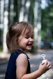 Baby blowing bubbles in a park. Small girl blowing bubbles outside in a park Royalty Free Stock Photo