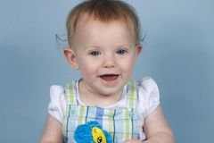 Baby on Blue. Baby holding toy flower smiling on a blue background Stock Images