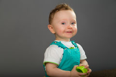 Baby in a blue bib pants Stock Images