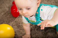 Baby in a blue bib pants Stock Photos