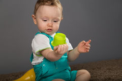 Baby in a blue bib pants Royalty Free Stock Image