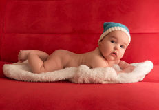 Baby in a blue cap, lying on a white skin Stock Photography