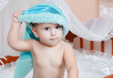 Baby in blue cap smiling in bed Stock Photos