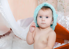 Baby in blue cap smiling in bed Royalty Free Stock Photo