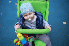 Baby with blue cap in stroller in autumn Stock Images