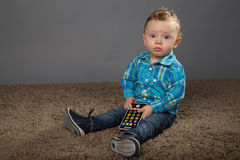 Baby in a blue checkered shirt. Playing with toys Stock Images