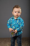 Baby in a blue checkered shirt. Playing with toys Royalty Free Stock Photos