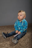 Baby in a blue checkered shirt. Playing with toys Stock Photo