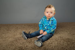 Baby in a blue checkered shirt. Playing with toys Stock Image