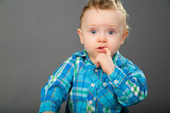 Baby in a blue checkered shirt. Playing with toys Royalty Free Stock Photo