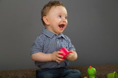 Baby in a blue checkered shirt. Playing with toys Stock Photography