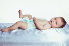 Baby with blue eyes lies in colors Stock Photos