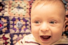 Baby with blue eyes playing at home Royalty Free Stock Image