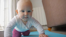 Baby with blue eyes trying to crawl on floor stock video footage