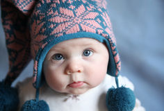 Baby with blue eyes in a winter cap. Portrait of an adorable baby girl with big blue eyes wearing a knit pink and blue winter hat Royalty Free Stock Photo