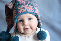 Baby with blue eyes in a winter cap. Portrait of an adorable baby girl with big blue eyes wearing a knit pink and blue winter hat Royalty Free Stock Photography