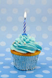 Baby blue first birthday cupcake. A home baked baby blue cup cake with a single lit candle to celebrate a first birthday or other anniversary Royalty Free Stock Photography