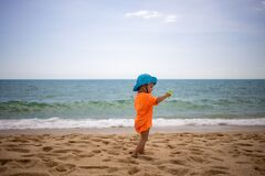 Baby in blue hat Walking On Beach. side View. end of quarantine, freedom of travel, open borders