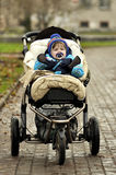 Baby in blue overalls sit in buggy. Serious baby in blue overalls sit in big three-wheeled buggy Stock Photography