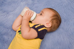 Baby on blue rug drinking bottle Stock Photos