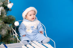 Baby in blue Santa Claus hat. Near Christmas tree Stock Photo