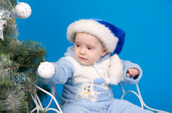 Baby in blue Santa Claus hat. Near Christmas tree Stock Photos