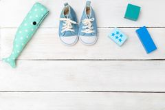 Baby blue shoes and toys on a white wooden background. View from Stock Photos