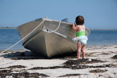 Baby with a boat. A baby girl standing by a boat looking out to sea Royalty Free Stock Photography