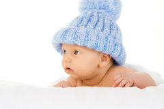 Baby in bobble hat. Portrait of cute baby boy in blue bobble hat, isolated on white background Royalty Free Stock Photography