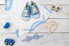 Baby bodysuit with blue shoes and baby toys on wooden background Royalty Free Stock Photography