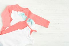 Baby bodysuit clothes over white wooden background. Copy space. Flat lay style. Pink and white wearing. Children fashion concept royalty free stock photo